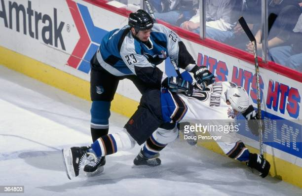 Shawn Heins of the San Jose Sharks slams Kelly Miller of the Washington Capitals into the wall face first at the MCI Center in Washington DC The...
