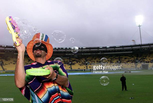 A masked fan amuses himself with bubbles after the first one day international between Australia and New Zealand at WestpacTrust Stadium was...