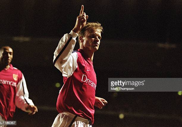 Dennis Bergkamp of Arsenal celebrates opening the scoring with a classic finish during the UEFA Champions League Group C match against Lyon played at...