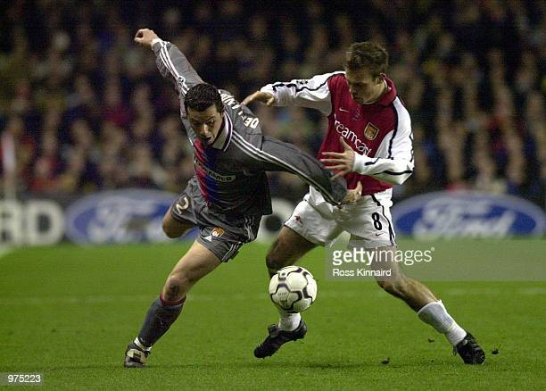 Fredrik Ljungberg of Arsenal tries to tackle Eric Deflandre of Olympique Lyonnais during the UEFA Champions League match between Arsenal and...