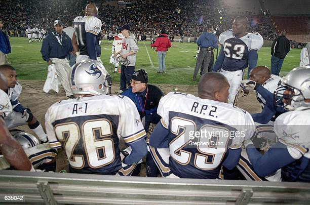 Head Coach Al Luginbill of the Los Angeles Xtreme discusses strategy with Dell 'A1' McGee and Ricky 'RP 2' Parker during the game against the Chicago...