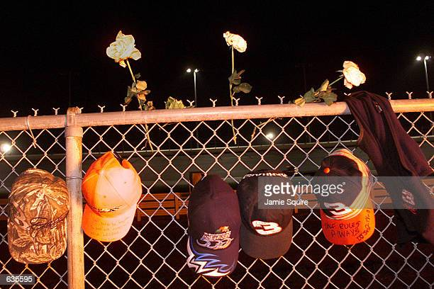 Saddened fans leave their caps in tribute on the fence at Turn 4 scene of the accident involving Dale Earnhardt who later succumbed to the injuries...