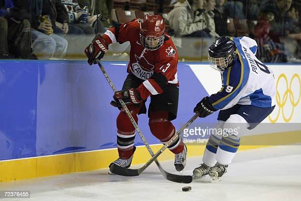 Caroline Ouellette of Canada is challenged by Olga Potapova of Kazakhstan in action in the women's ice hockey preliminary round match between Canada...