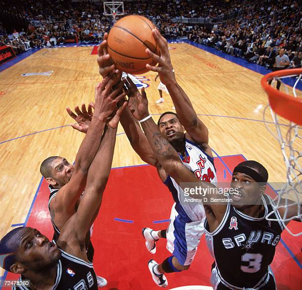Center Michael Olowokandi of the Los Angeles Clippers and two San Antonio Spurs guard Stephen Jackson and forward Tim Duncan attempt to rebound the...