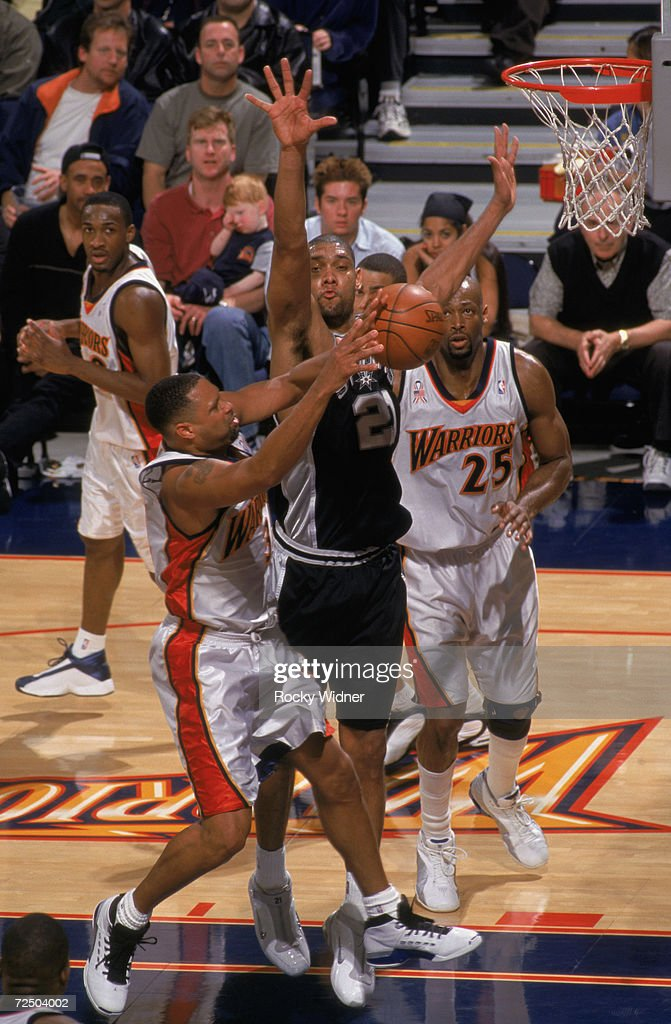Center Tim Duncan of the San Antonio Spurs goes to block forward Chris Mills of the Golden State Warriors during the NBA game at the Arena in Oakland...