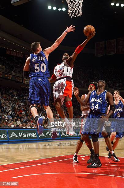 Cuttino Mobley of the Houston Rockets goes around Mike Miller of the Orlando Magic goes for a layup at the Compaq Center in Houston Texas DIGITAL...