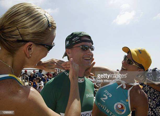 Eddie Irvine of Jaguar Racing gets some suncream applied by Kerry Pottharst and Natalie Cook Australian Beach Vollyball Olympic Gold Medalists before...