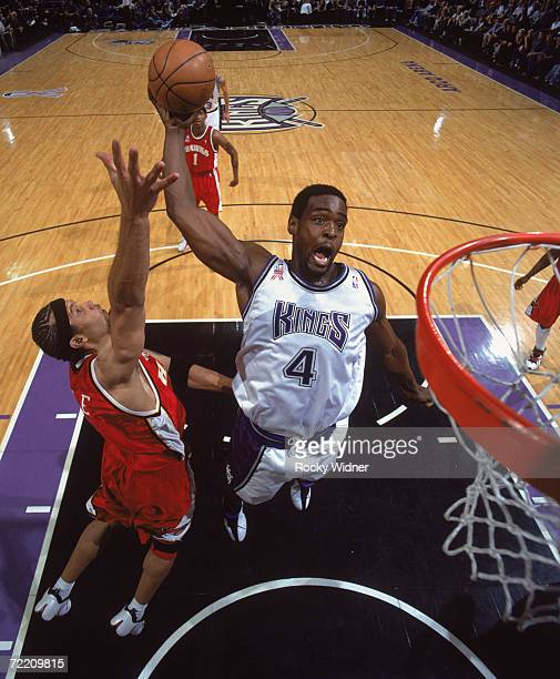Forward Chris Webber of the Sacramento Kings dunks past forward Ira Newble of the Atlanta Hawks during the NBA game at Arco Arena in Sacramento...