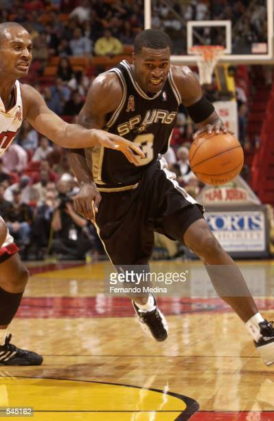 Guard Stephen Jackson of the San Antonio Spurs drives past forward LaPhonso Ellis of the Miami Heat during the NBA game at American Airlines Arena in...