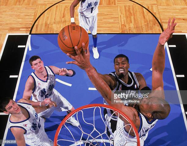 Guard Stephen Jackson of the San Antonio Spurs shoots over forward Don Reid of the Orlando Magic during the NBA game at the TD Waterhouse Centre in...