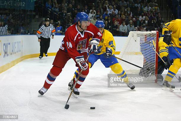 Milan Hejduk of the Czech Republic carries the puck behind the Swedish net while being pursued by Tomas Holmstrom of Sweden during the Salt Lake City...