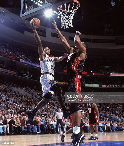Point guard Eric Snow of the Philadelphia 76ers shoots the ball as center Alonzo Mourning of the Miami Heat attempts to block during the NBA game at...
