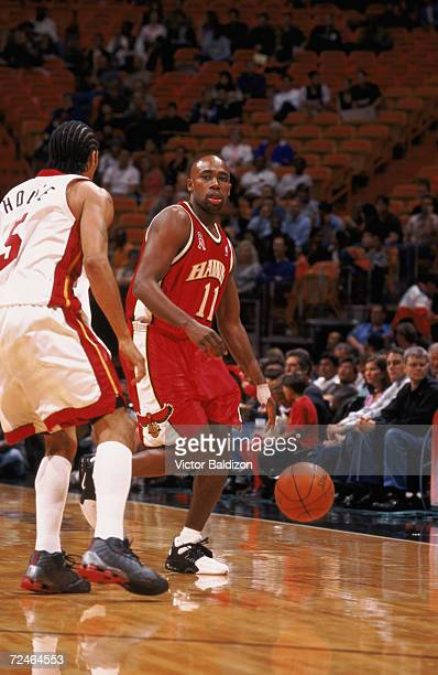 Point guard Jacque Vaughn of the Atlanta Hawks dribbles around guard Eddie House of the Miami Heat during the NBA game at American Airlines Arena in...