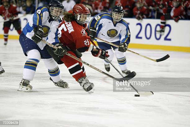 Tammy Lee Shewchuk of Canada is challenged by Olga Potapova of Kazakhstan in the women's ice hockey preliminary round match between Canada and...