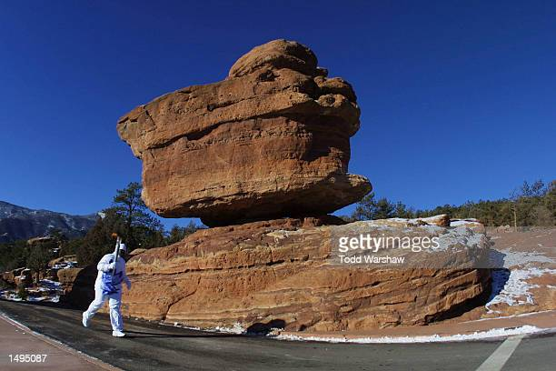 Torchbearer Lawrence Riddick carries the Olympic Flame past Balance Rock in Garden of the Gods State Park during the 2002 Salt Lake Olympic Torch...