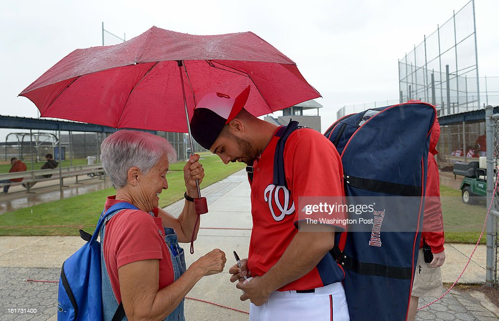 Nena Stevens of Winter Park, Fl holds an umbrella for Washington Nationals starting pitcher Gio Gonzalez (47) as a heavy rain falls cutting short their first spring training workout on February 14, 2013 in Viera, FL