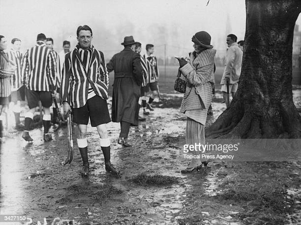 A young woman approaches Oxford Captain D H Scott at a university hockey match between Oxford and Cambridge at Beckenham