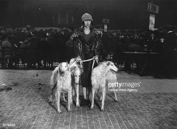 Miss Vlasto stands with her Borzoi dogs in the exhibition ring having entered them in the Crufts Dog Show at the Royal Agricultural Hall in Islington...