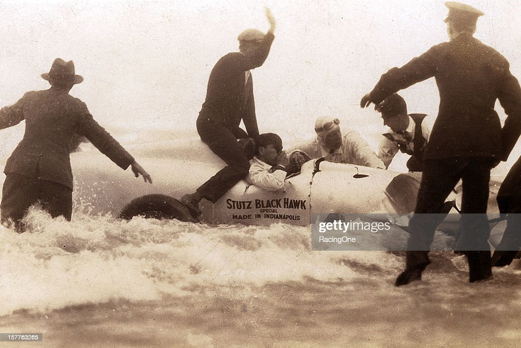 Spectators assist Frank Lockhart after he flipped the Stutz Blackhawk endoverend into the surf while attempting a world land speed record run on...