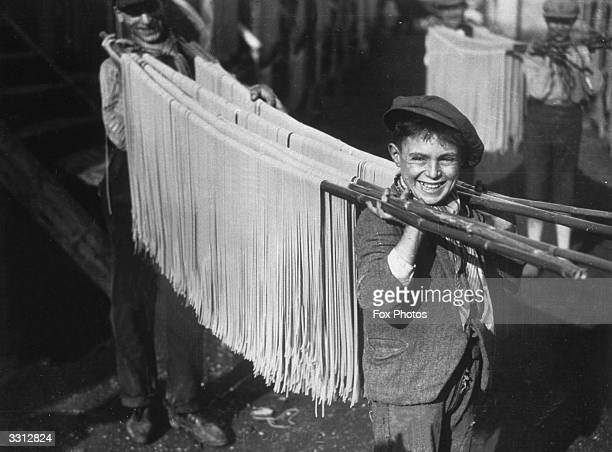 A young boy carrying strings of pasta in a macaroni factory in Naples Italy