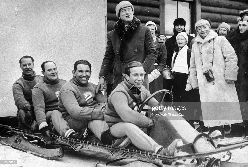 Fulllength image of the four American athletes comprising the United States Olympic bobsled team seated in their bobsled with smiling onlookers Lake...