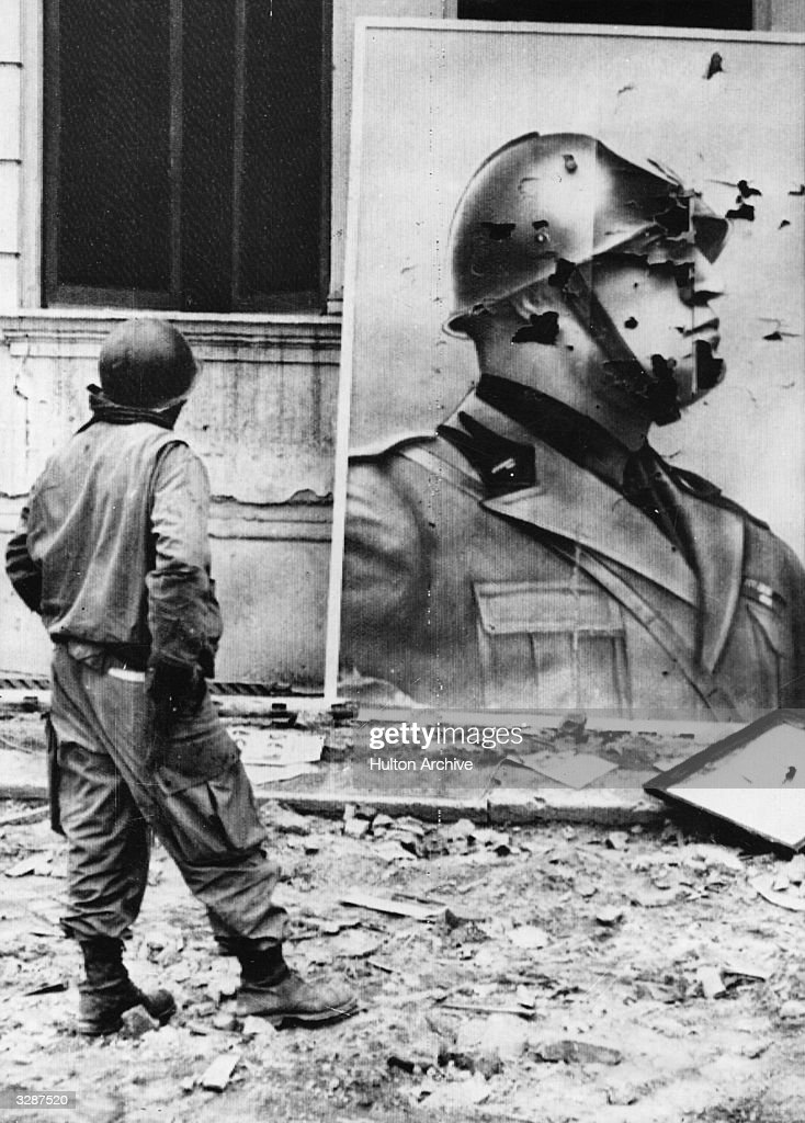 An American soldier looks at a bullet-riddled poster of the Italian Dictator Benito Mussolini (1883 - 1945) near the Anzio beachhead.