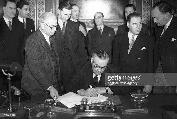 English foreign secretary Ernest Bevin signing the Peace Treaties with Italy Hungary Bulgaria Romania and Finland at the Foreign Office in London...