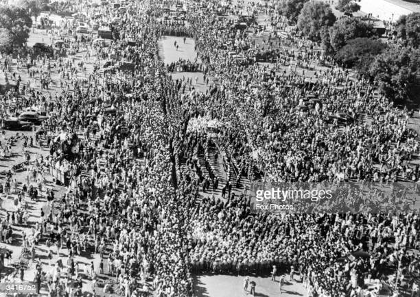 A crowd watching the funeral procession of Indian statesman and advocate of nonviolence Mahatma Gandhi who was assassinated in Delhi