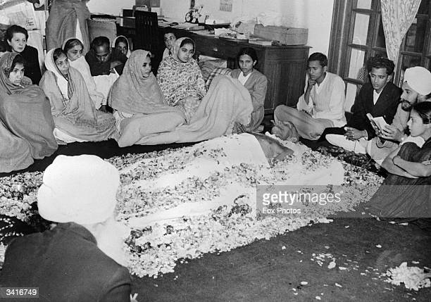 A Sikh priest reciting the scripts from the Gurugranth Saheb while the body of Indian statesman and advocate of nonviolence Mahatma Gandhi lies in...