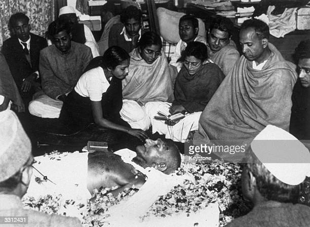 The niece of Mahatma Gandhi places flower petals on his brow as he lies in state at Birla House New Delhi after his assassination Immediately after...