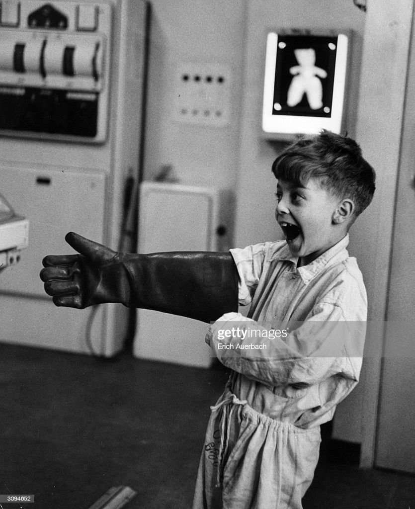 A young boy in pyjamas has fun playing with a radiographer's protective glove at Leeds General Infirmary part of a plan to take the fear away from...