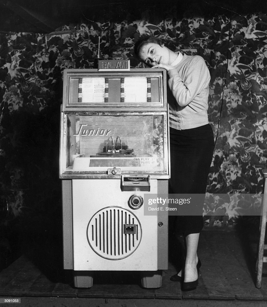 A young woman gets dewy-eyed with the music from a juke box. Original Publication: Picture Post - 9123 - Girl With A Juke Box - pub. 1957
