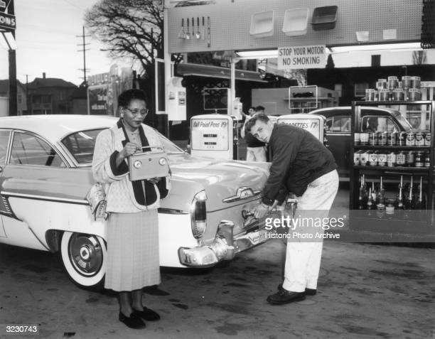 An AfricanAmerican woman holds a transistor radio contest prize as a Caucasian male service station attendant puts gas into her car gas tank looking...