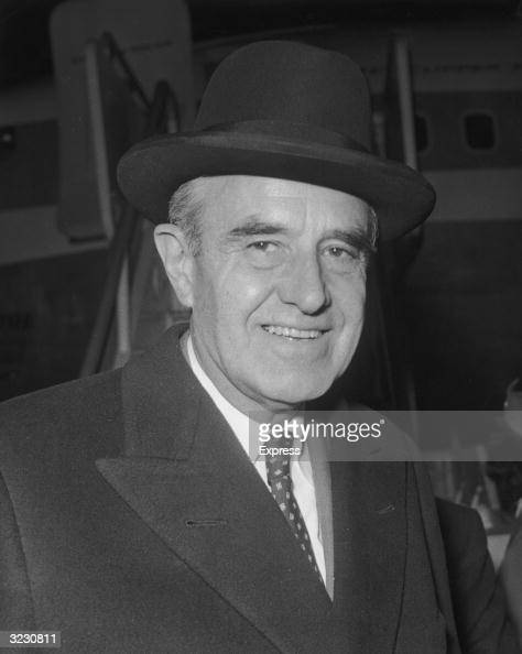 Headshot of American diplomat William Averell Harriman in front of an airplane ramp at an airport in London England