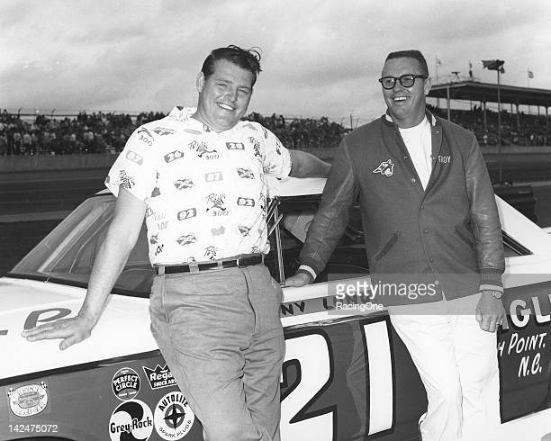 """Gentle giant drivers Dwayne """"Tiny"""" Lund and Troy Ruttman relax in street clothes next to Lund's Wood Brothers Ford prior to the running of the..."""