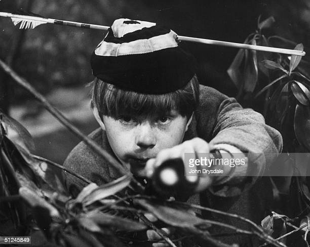 February 1963 Peering through the bushes with an arrow through his school cap 13 year old actor Denis Gilmore as 'William' from the 'Just William'...