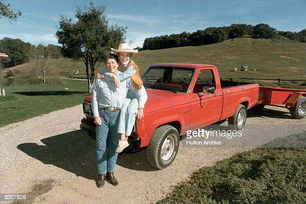 A fulllength portrait of United States president Ronald Reagan and First Lady Nancy Reagan who is sitting on the hood of a red 1985 Ford Ranger...