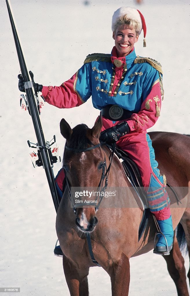 Tina Windscheid on horseback. She is wearing a distinctive ski suit designed by Bogner and carrying a pair of skis.