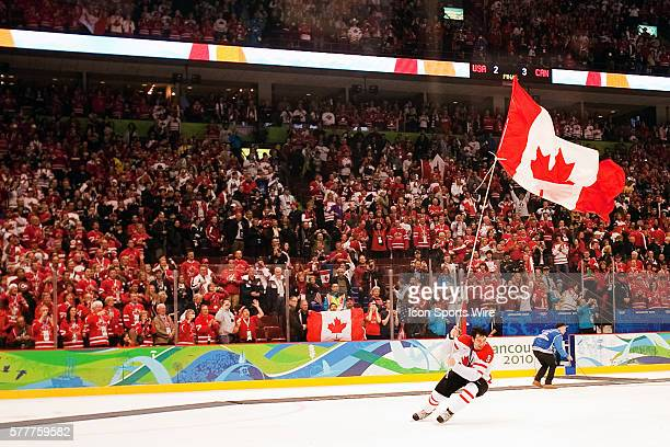 Canada's Drew Doughty celebrates the victory by carrying the Canadian flag around the ice at the end of the Gold medal Hockey Final between the...