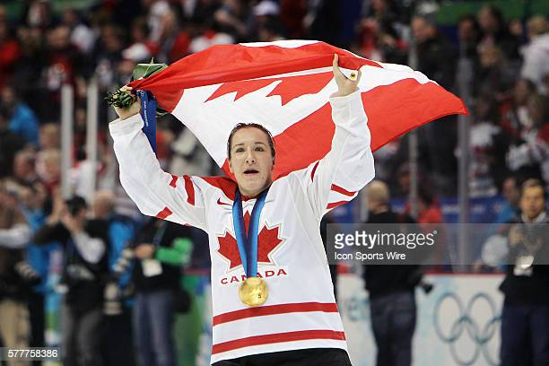 Team Canada player celebrates with her country's flag and her new gold medal at the end of the Women's Ice Hockey Gold Medal Game between Canada and...
