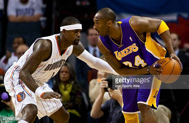 Los Angeles Lakers shooting guard Kobe Bryant looks to drive around Charlotte Bobcats shooting guard Stephen Jackson during an NBA basketball game at...