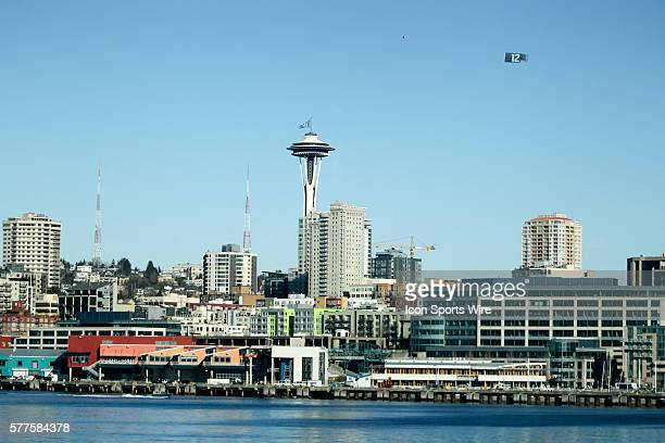 A plane flies over Seattle pulling a 12th man flag while a 12th man flag waves atop the Seattle Space Needle Seattle Seahawks players and 12th man...