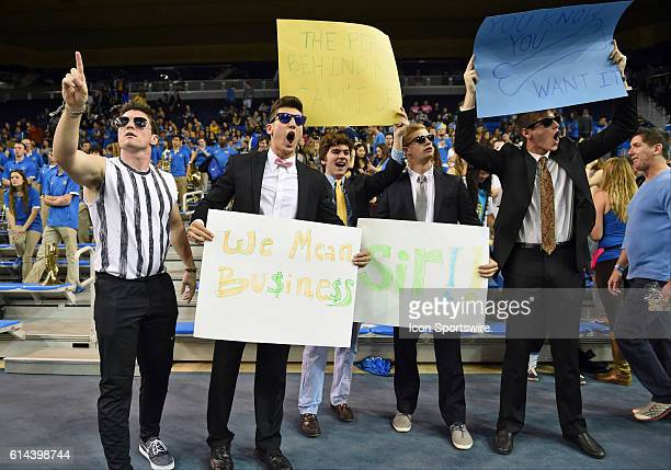 UCLA student fans dressed up in business attire taunt the Huskies during an NCAA basketball game between the Washington Huskies and the UCLA Bruins...