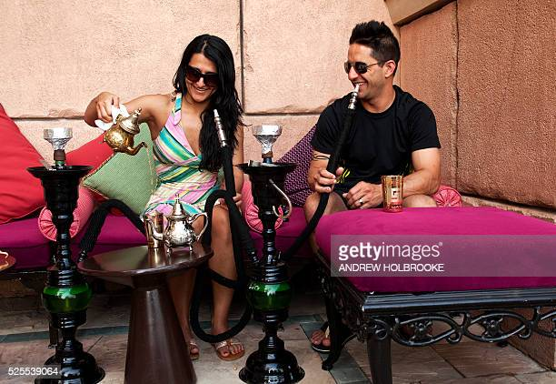 February 22 2012 American tourists staying at the 5 star Atlantis Hotel Dubai on Palm Jumeirah smoke a hookah and pour tea