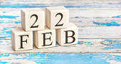 February 22th. Wooden cubes with date of 22 February on old blue wooden background.