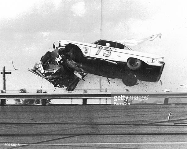 Lee Petty and Johnny Beauchamp sail over the turn four railing of Daytona International Speedway after tangling on lap 37 of the second qualifier for...