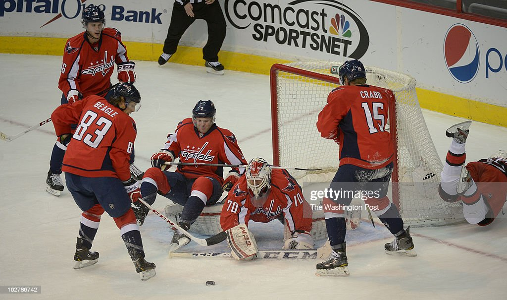 Washington Capitals goalie Braden Holtby (70) gets pleanty of help from his teammates as a shot bounces around during 1st period action against the Carolina Hurricanes on February 26, 2013 in Washington, DC