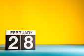 February 28th. Day 28 of february month, calendar on yellow background. Winter time. Empty space for text.
