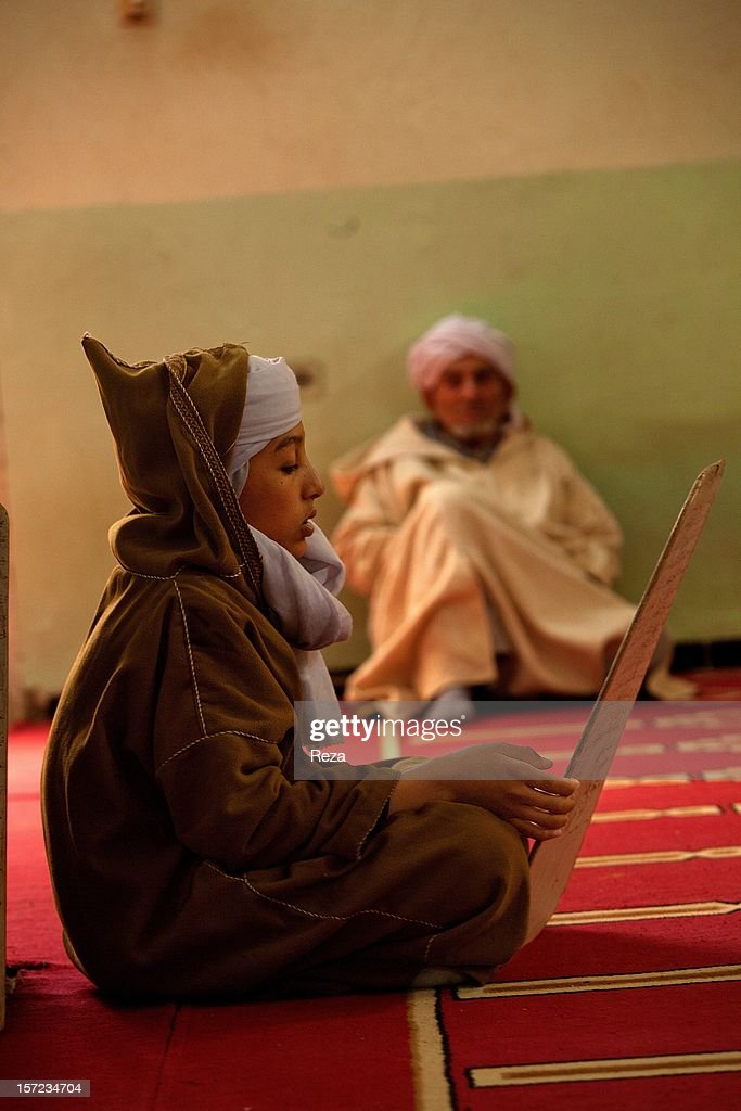 February 6th, 2012, village of Oued Bou Ali near Timimoun, Algeria. On the anniversary of the birth of Prophet Muhammad, a student is reading the Koran under the watchful eye of a visitor who has come to rest in this religious boarding school located near Timimoun.