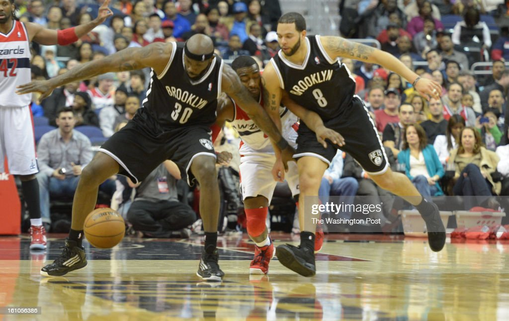 Washington Wizards point guard John Wall gets sandwiched by Brooklyn Nets power forward Reggie Evans and guard Deron Williams going after a loose...